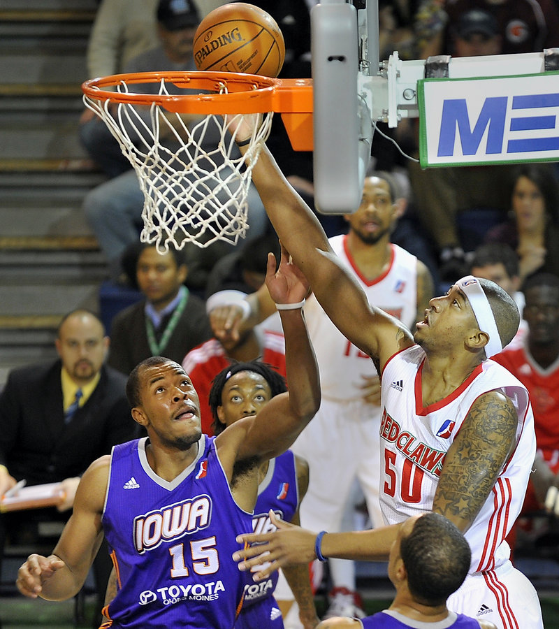 Magnum Rolle of the Maine Red Claws puts back an offensive rebound Friday night in front of Marqus Blakely of the Iowa Energy in the first quarter at the Portland Expo. The Red Claws lost 99-90 and fell to 14-25 on the season.
