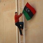 A Libyan rebel climbs to put a pre-Moammar Gadhafi flag on the roof of a government building after fighting against troops in the oil town of Ras Lanouf on Saturday.