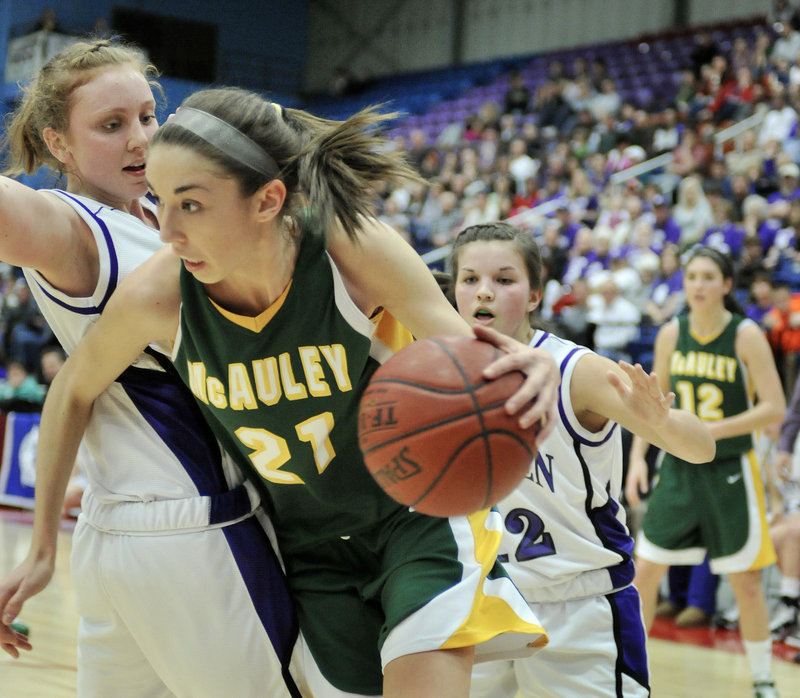 Alexa Coulombe of McAuley tries to drive past Courtney Doyon of Hampden Academy during the Class A girls' basketball state final Saturday at the Augusta Civic Center. Coulombe had 15 points in the Lions' 39-23 victory.