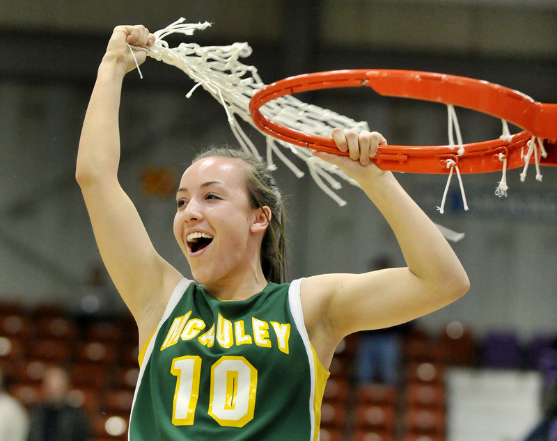 Kayla Daigle gets a fistful of net after the McAuley High basketball team beat Hampden Academy 39-23 in the Class A girls' state championship game Saturday at the Augusta Civic Center.