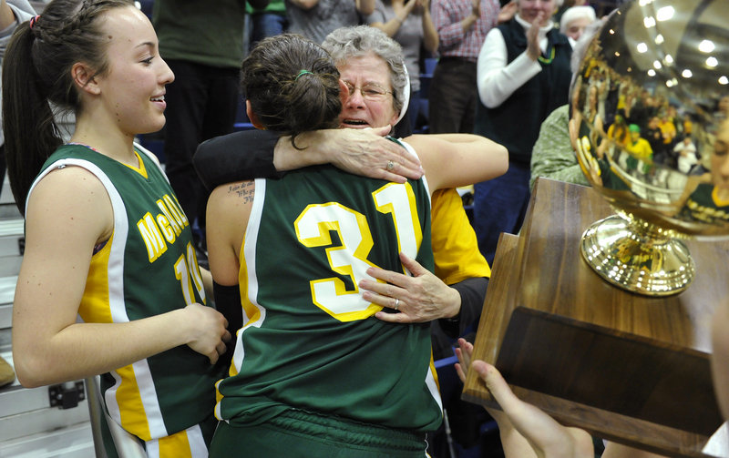 Rebecca Knight shares a hug with longtime McAuley supporter Sister Edward Mary as she and Kayla Daigle take to the stands to celebrate the Lions 39-23 victory over Hampden Academy in the Class A state title game Saturday.