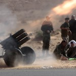 Libyan rebels fire multiple launcher rockets against government forces near the town of Bin-Jawad in eastern Libya on Sunday. Thousands of leader Moammar Gadhafi's supporters poured into the streets of Tripoli on Sunday, waving flags and firing their guns into the air.