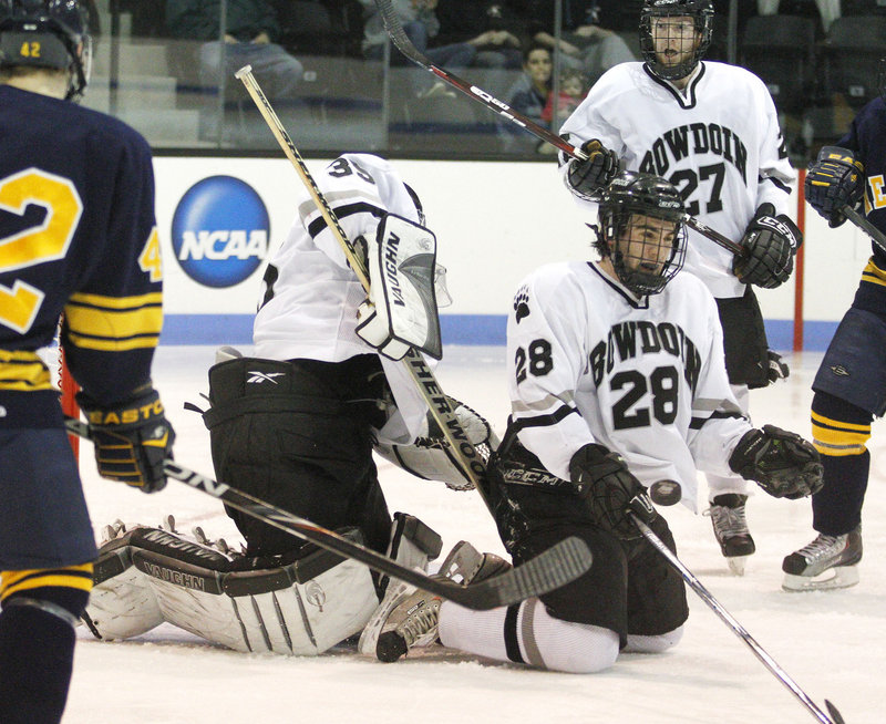 Bowdoin goalie Steve Messina gets help from defenseman Timothy McGarry, who blocks a shot with his body during an NCAA Division III tournament game Wednesday night at Brunswick. Bowdoin advanced by beating Neumann University, 2-1.