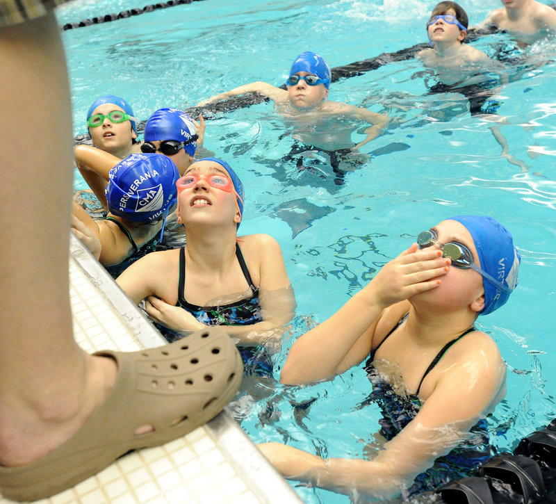 Caroline Corbeau, left, and Maria Smith of Cape Elizabeth receive some last-minute instructions before the 400-yard freestyle relay for girls 10 and under.