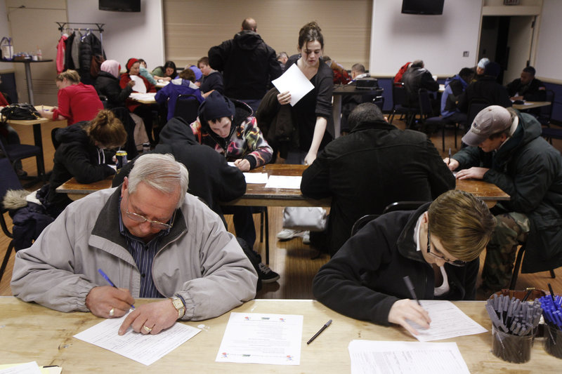 Charles Truesell of North Yarmouth and Frances Mahoney of Scarborough fill out Renys applications during a job fair at the Cumberland County Civic Center in Portland on Friday.