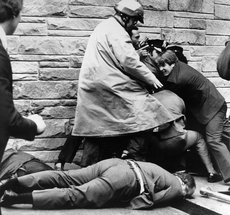 White House press secretary James Brady, badly wounded in the head, lies on the sidewalk on March 30, 1981. Behind him, Secret Service agents and police officers wrestle shooter John Hinckley Jr. to the ground.