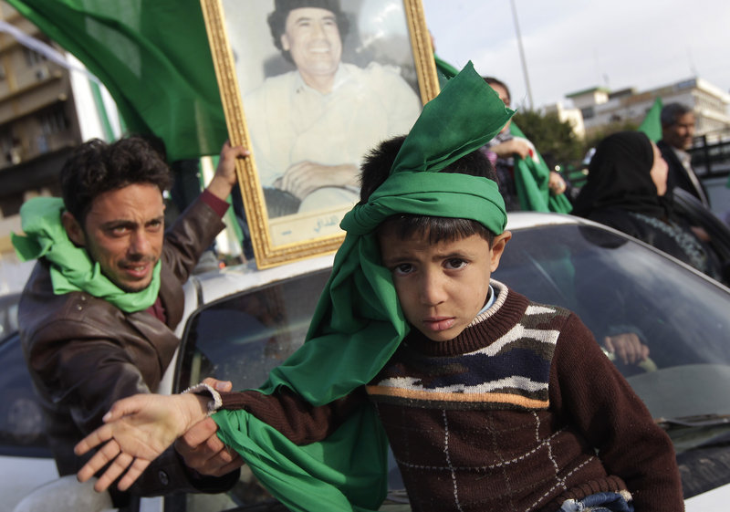 A supporter of Libyan leader Moammar Gadhafi coaxes a child to raise his arm for the photographer during a government-organized visit for foreign media Friday in Zawiya, 30 miles west of Tripoli. Gadhafi's regime has gained momentum with the capture of Zawiya.