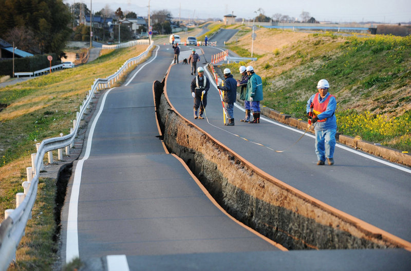 Workers inspect a caved-in section of a prefectural road in Satte, Saitama Prefecture, on Friday.