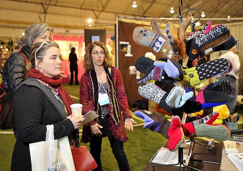 Marilyn Robertson of York Harbor-based Jack and Mary Handbags, right, talks to Julia Dickenson, front, of Norwich, Vt., and Ingrid Ellison of Camden at the New England Products Trade Show on Saturday.