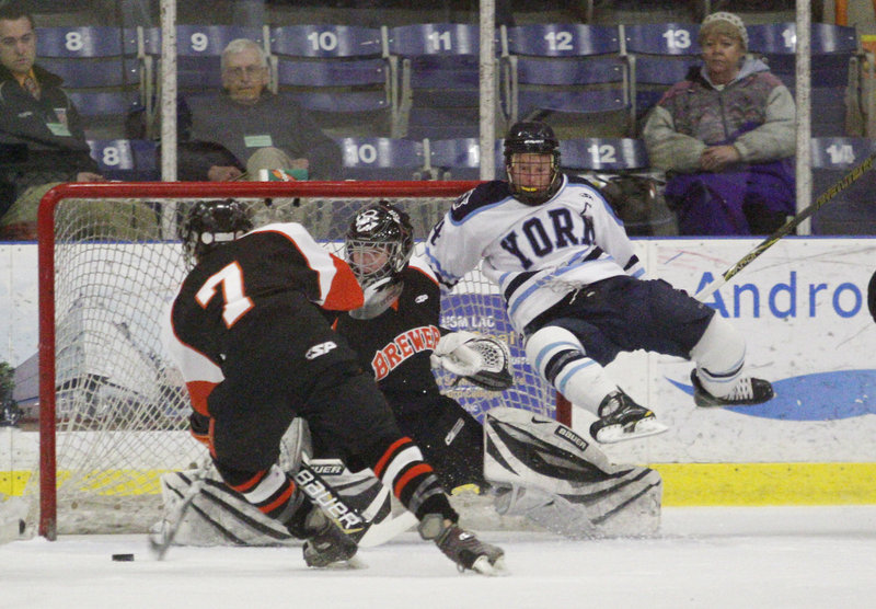Jake Valley of Brewer clears the puck from in front of goalie Adam Cossette as Anthony Figlioli of York heads to the ice in the first period of the Class B championship game.
