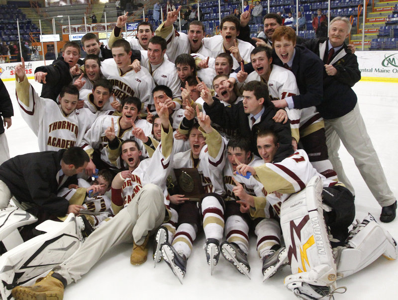 The Thornton Academy hockey team poses with the state Class A championship plaque Saturday after beating Lewiston 4-3 in double overtime. The Trojans won their first trip to the state final, as the Blue Devils lost in the state championship game for a fifth straight season.