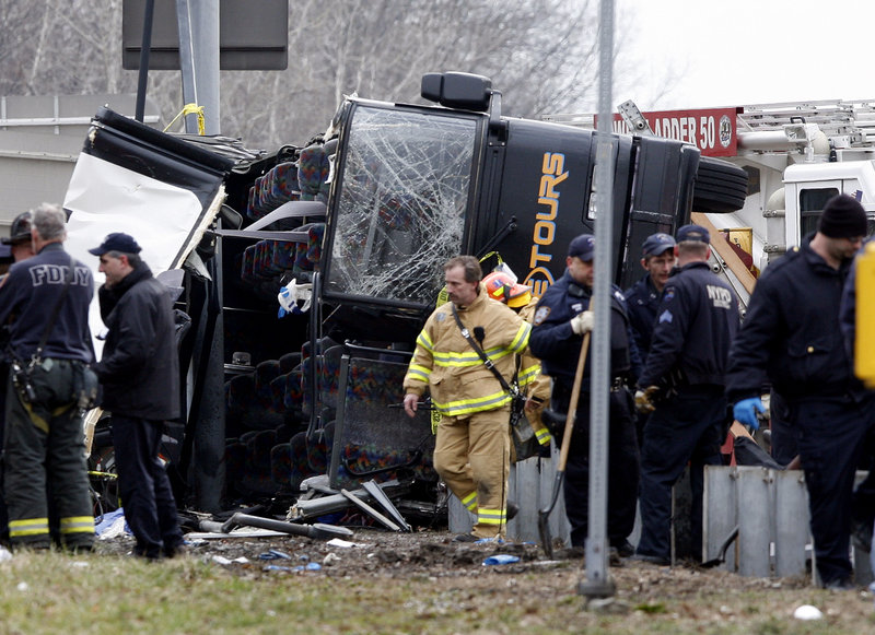 Rescue workers investigate a bus crash in the Bronx on Saturday. Fourteen people died in the accident.
