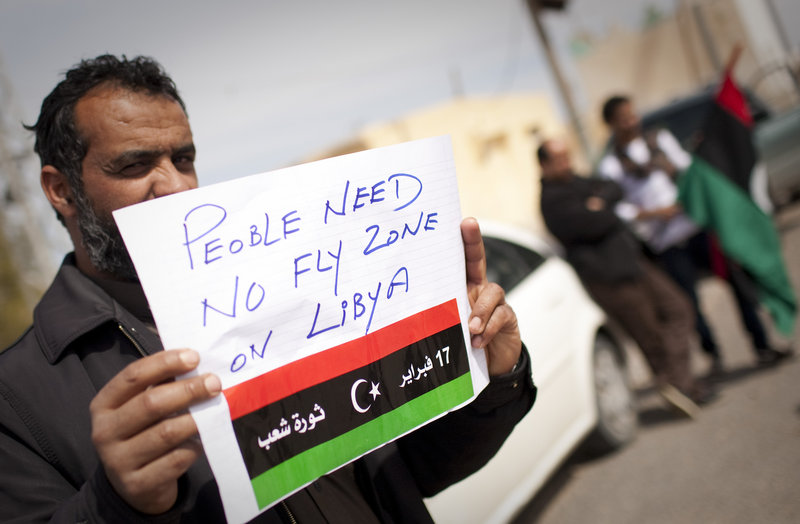 A Libyan man holds up a sign asking for a no-fly zone over Libya near the town of Musa'id on Sunday. Moammar Gadhafi's forces swept rebels from one of their final strongholds on Libya's main coastal highway, after waves of strikes from warships, tanks and warplanes.