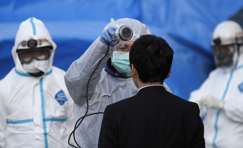 A worker scans a man for radiation exposure in Koriyama, Japan, on Sunday. So far, about 160 people show signs of exposure.