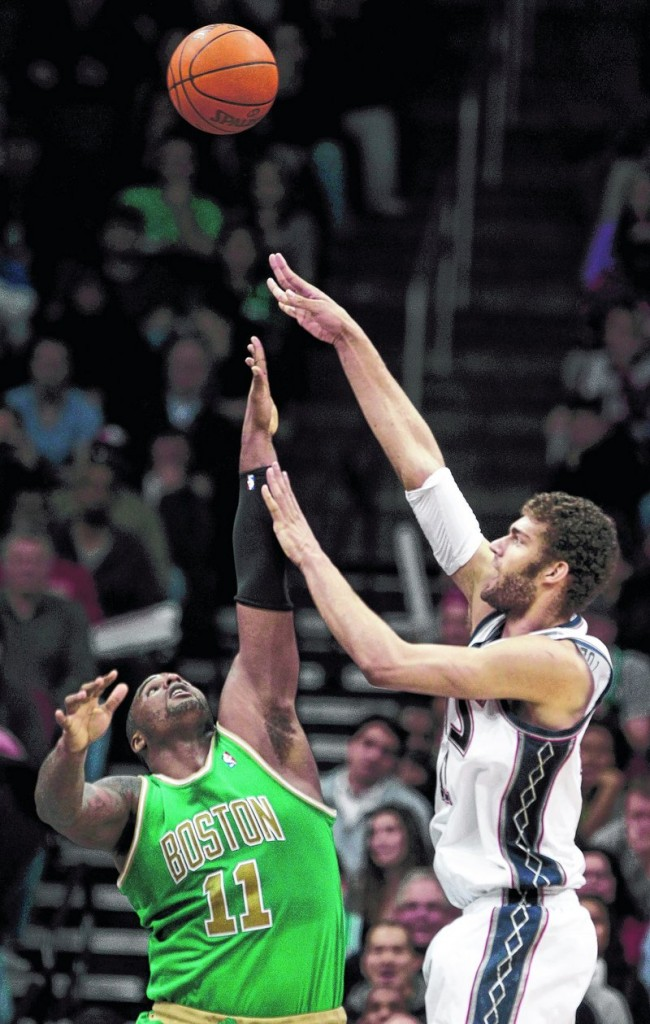 Brook Lopez, who scored 20 points Monday night for the New Jersey Nets, takes a shot over Glen Davis of the Boston Celtics in the first quarter of the Nets' 88-79 victory.