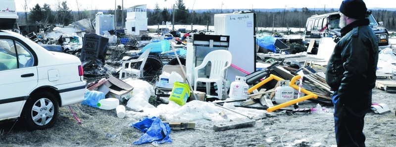 Jim Saucier looks over the yard filled with household items and vehicles Monday at a mobile home where three adults were killed in a fire in Unity Township a day earlier.