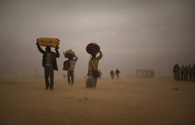 Migrant workers fleeing the unrest in Libya carry their belongings through a sandstorm in a refugee camp in Ras Ajdir, Tunisia, on Tuesday. More than 250,000 migrant workers have left Libya in the past three weeks.