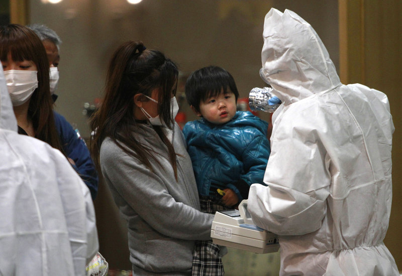 A child is screened for radiation exposure Tuesday at a testing center in Koriyama city, Fukushima prefecture, Japan. The Dai-ichi nuclear power plant on the prefecture's coast was damaged by explosions and has been leaking radiation for days.