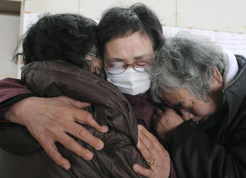 Survivors huddle in mourning at a Kesennuma, Japan, evacuation center after learning Tuesday of the death of relatives in the quake and tsunami.