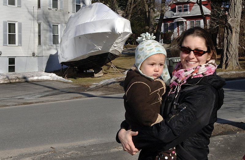 Kim Meyers, holding her daughter, Iris, says having boats stored in the neighborhood is a normal part of winter.