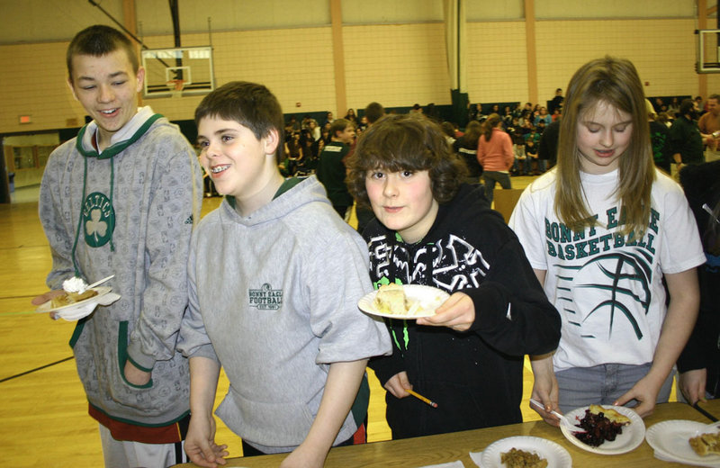 Bonny Eagle Middle School students, from left, Reid Wallingford, Josh Grant, Ryder Kallweit and Desiree Wright have a slice of pie during the school's annual Pi Day event celebrating mathematics. A variety of mathametics awards were presented during the event.