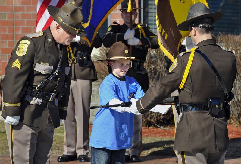 "Guided by Sgt. Paul Thorpe, left, Cameron Tufts, 9, of New Gloucester takes part in a ""white glove military inspection"" as he gets to be ""Deputy Sheriff for a Day"" on Thursday in Portland."