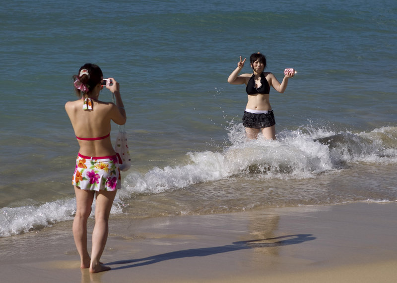 Two visitors from Japan take pictures at Waikiki Beach in Honolulu on March 11. Hawaii is bracing for a loss in tourists from Japan as a consequence of the earthquake, tsunami and nuclear crisis in that nation.