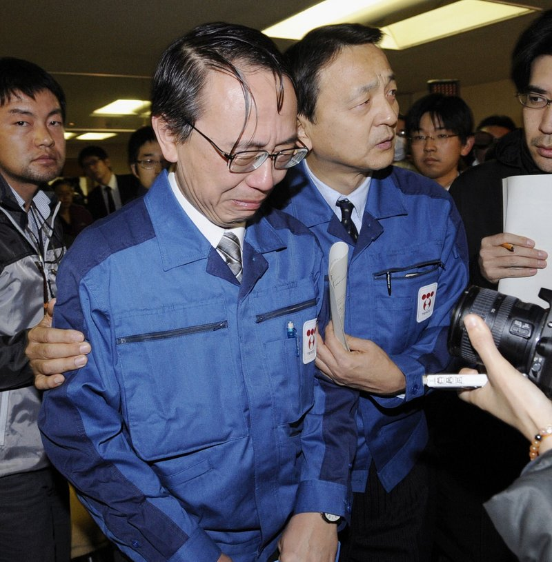 Tokyo Electric Power Co. Managing Director Akio Komori, center, sheds tears as he leaves a news conference in Fukushima on Friday, a week after an earthquake and resulting tsunami triggered a historic nuclear crisis in Japan.