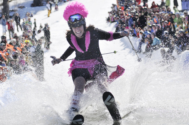 Janice Perrin gives it her all as she tries to cross 100 feet of water on skis during the Slush Cup contest at Shawnee Peak in Bridgton on Saturday.