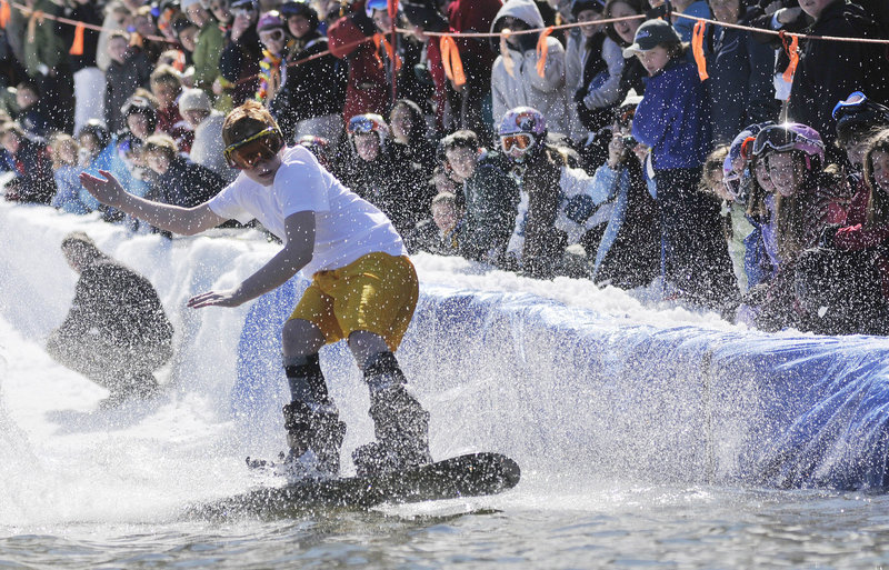 Chris Anderson of Massachusetts rides a snowboard across the man-made pond.