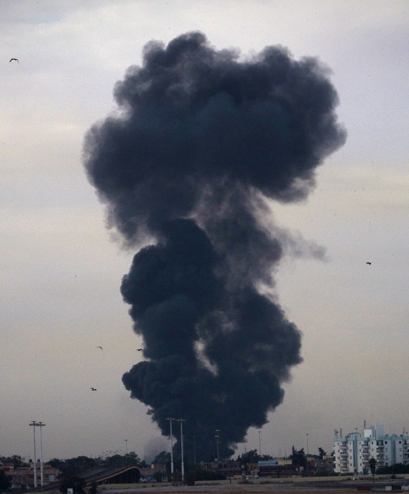 Smoke billows from the site where a plane was shot down Saturday near Benghazi, a rebel stronghold in eastern Libya that has been the focus of Gadhafi loyalists.