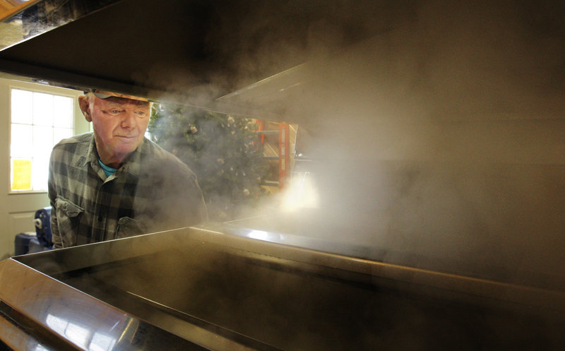Bob Michaud checks on sap boiling in an evaporator at the Thurston and Peters Sugarhouse in Newfield.