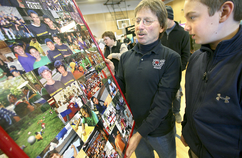 Steve Lepler, director of the West End House Camp in East Parsonsfield, holds a photo collage at Sunday's camp fair so Alex Smith, 12, of Portland can look for friends who attended the camp.
