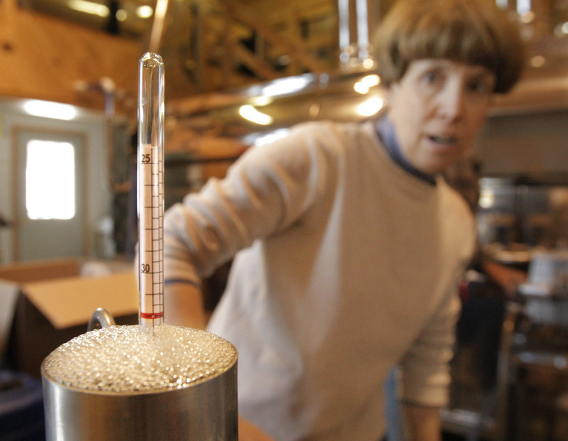 Debra Hartford looks at a hydrometer to check the density of syrup that is about to be bottled at the Thurston and Peters Sugarhouse.