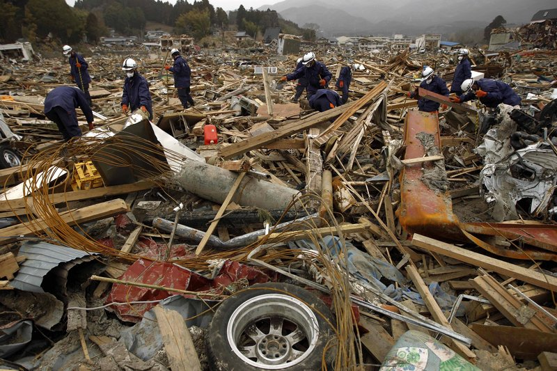 Police officers search through debris in a residential area destroyed by the March 11 earthquake and tsunami in Rikuzentakata, Iwate Prefecture, Japan, on Sunday. The safety of food and water is a growing concern in Japan.