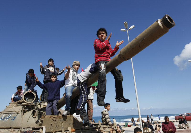 Libyan boys sitting on the cannon of a destroyed army tank celebrate the freedom of Benghazi on Monday. U.S., British and French warplanes, enforcing a U.N. resolution, bombarded government armored vehicles as they fled the city Sunday.