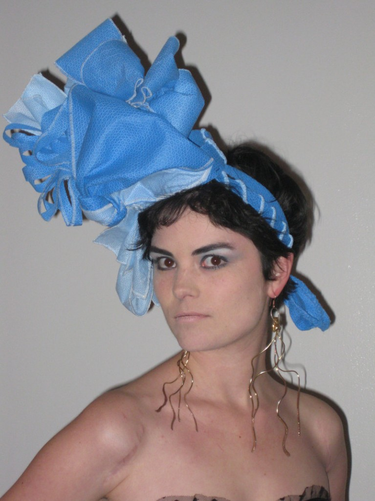 Beth Schneider models a blue wrap headdress designed by Gabriella Sturchio.