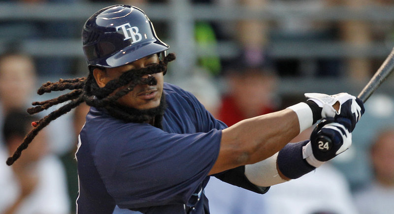 With his dreadlocks wrapped around his face, Tampa Bay's Manny Ramirez swings and misses at a pitch during the second inning of a spring training game Tuesday against Boston in Fort Myers, Fla. Ramirez walked on the at-bat.