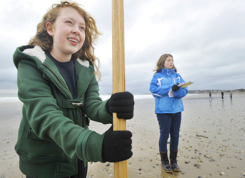 Genny Guibord, left, and Scarborough Middle School classmate Sarah Griffin record the slope of the beach as part of the Southern Maine Beach Profile Monitoring Project.