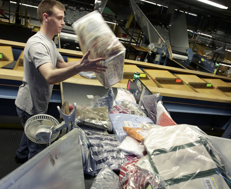 Justin Reil of Brunswick handles merchandise for shipping at an L.L. Bean facility in Freeport on Thursday. A spokesman says the company's free shipping offer comes with no strings attached.