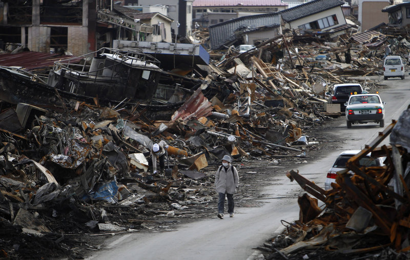 A resident of Kesennuma, Miyagi Prefecture in northern Japan walks between the rubble caused by the March 11 tsunami. Some 660,000 households still do not have water, the government said.