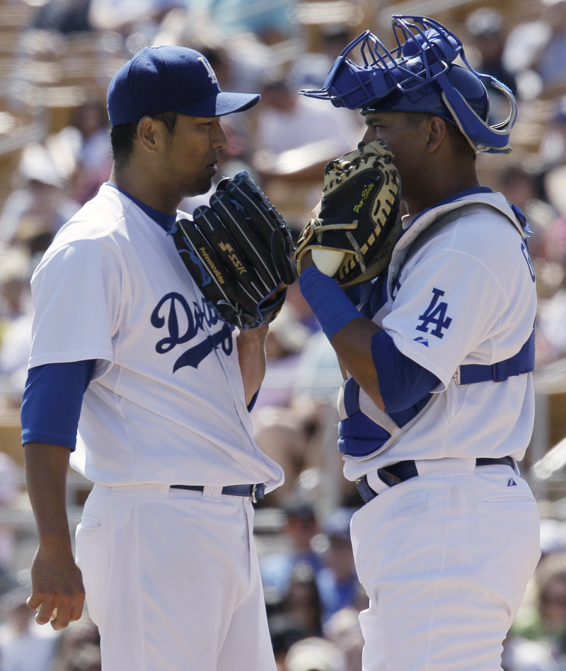 The Dodgers' Hiroki Kuroda, left, and catcher Hector Giminez are awfully secretive for a spring training game. It didn't help as Colorado scored seven times in the ninth inning for a 7-5 win.