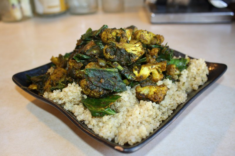 A curry with onions, eggplant, cauliflower, spinach and collard greens, which is served on a bed of quinoa. Find recipes for similar curries on Norster's blog.