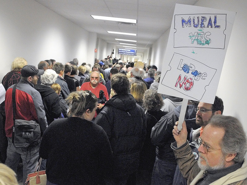 Roy Patterson, right, of Gray holds a sign expressing his feelings as hundreds of protesters listen to speeches at a noon rally Friday at the Department of Labor in Augusta. The event was organized by the Maine Union of Visual Artists and the Maine AFL-CIO to protest Gov. Paul LePage's order to remove a 36-foot, 11-panel mural from the building. The artwork, by Judy Taylor of Tremont, was installed in 2008.