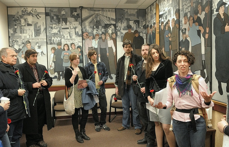 Jessica Graham, right, of Waterville leads a prayer Friday morning in the lobby of the Maine Department of Labor to mark the 100th anniversary of the Triangle Shirtwaist factory fire in New York City, which killed 146 workers. The rally, the first of two Friday to protest the proposed removal of the mural in the background, included the placing of red carnations on a table by the panel depicting the 1937 strike at the Lewiston-Auburn shoe shops.