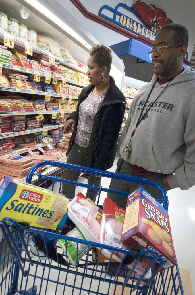 Andrea Long and Darryl Witherspoon select some Clear Value products at a Bi-Lo supermarket in Charlotte, N.C. Since the recession's onset, store brands' sales have grown.