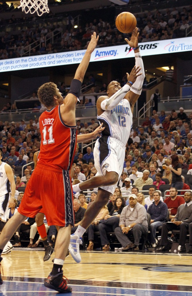 Dwight Howard lifts a shot over New Jersey's Brook Lopez on Friday. The Magic scored a 95-85 win after New Jersey rallied for a 68-66 lead in the fourth quarter.
