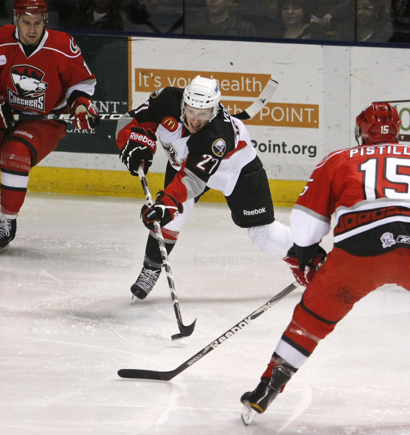 Mark Voakes of the Pirates sends a shot toward the goal while Matthew Pistilli and Jon Matsumoto, left, defend. Voakes scored at the end of the first period of Portland s 5-4 loss.
