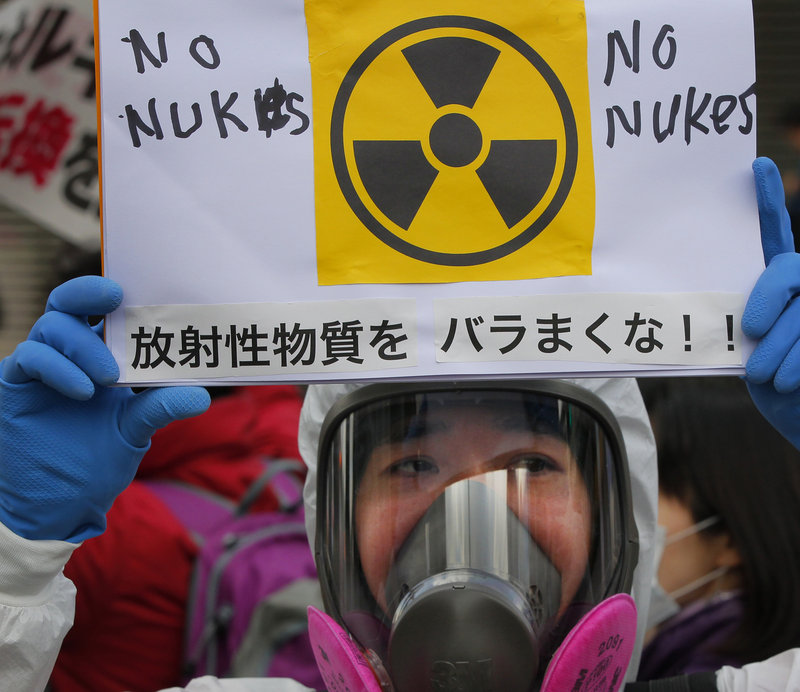 A protester in a protective mask holds a placard during an anti-nuclear rally in Tokyo on Sunday. The nuclear plant crisis has spurred concerns about the safety of food and water in Japan. Radiation has been found in food, seawater and even tap water supplies in Tokyo.