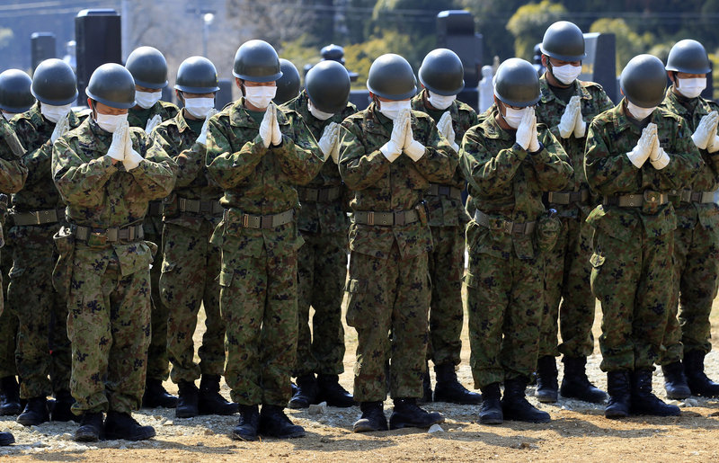 Members of the Japan Ground Self-Defense Force pray Tuesday for victims of the March 11 earthquake at a mass grave site in Yamamoto, in northeastern Japan. With thousands of bodies stored in makeshift morgues, local governments are forced to bury bodies in mass graves.